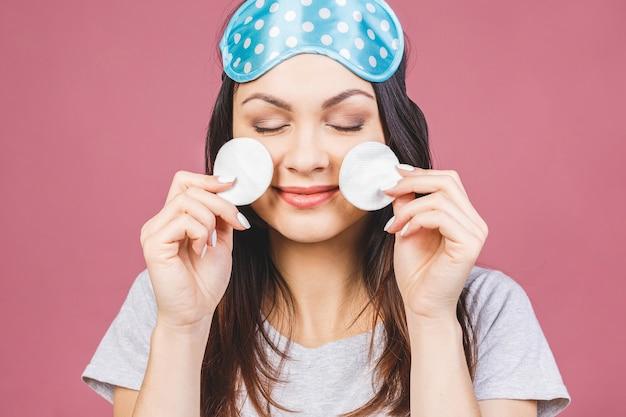 Fille fraîche en bonne santé, démaquillant de son visage avec un coton. beauté femme nettoyant son visage avec un coton-tige isolé sur fond rose. concept de soins et de beauté de la peau. masque de sommeil.