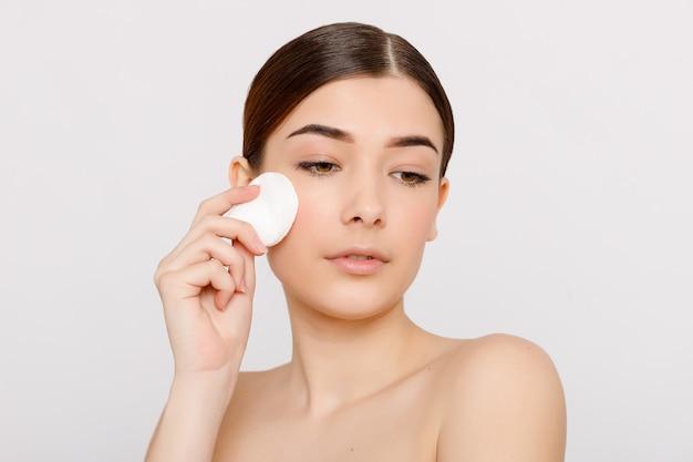 Fille fraîche en bonne santé enlevant le maquillage de son visage avec un coton. femme de beauté nettoyant son visage avec un coton-tige isolé sur fond gris. concept de soins de la peau et de beauté.