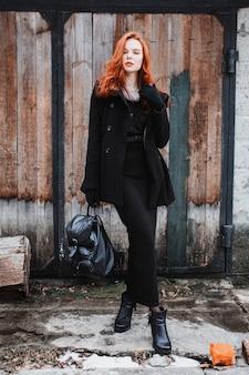 Fille frappante aux longs cheveux roux dans des vêtements noirs. une femme dans un manteau noir et sac à dos en mains posant sur le fond du vieux mur. style de mode de rue féminine. beau modèle rousse élégant