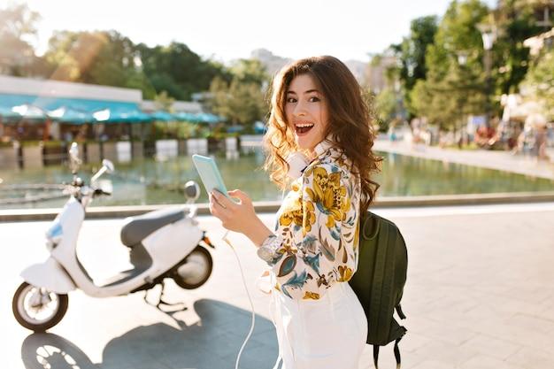 Une fille frisée excitée avec un sac à dos noir a reçu un nouveau message de sa meilleure amie qu'elle attendait près de la fontaine principale de la ville
