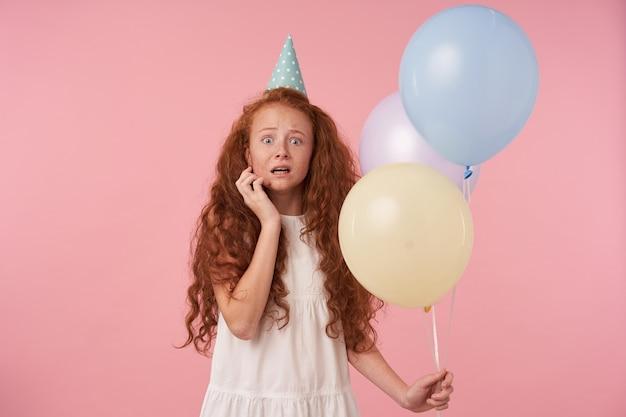 Fille frisée hredhead effrayée aux cheveux longs portant une robe élégante blanche, gardant la main sur son visage et regardant à peine à la caméra, isolée sur fond rose avec des ballons à air à la main