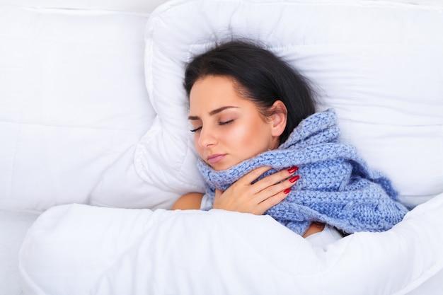 Fille avec froid couché sous une couverture