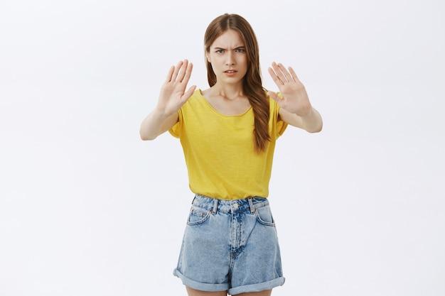 Fille fronçant les sourcils déçue montrant un geste d'arrêt, interdire ou refuser quelque chose d'omnieux