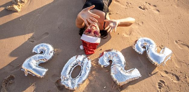 Fille gaie avec des boules argentées sous forme de nombres 2022 près du concept de mer du nouvel an