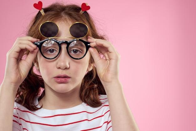 Fille gaie avec des lunettes de soleil tresses t-shirt rayé lifestyle rose