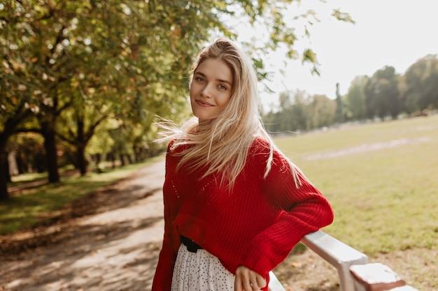Fille gaie avec un maquillage naturel souriant volontiers. jolie blonde posant joyeusement dans le parc d'automne.