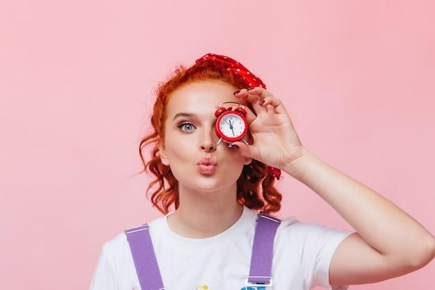 Une fille gaie en t-shirt blanc souffle un baiser et couvre les yeux avec un réveil