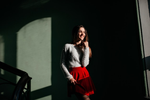 Fille galbée en jupe rouge debout dans le noir et souriant