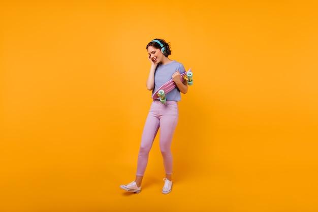 Fille galbée en tenue décontractée colorée, écouter de la musique dans les écouteurs. modèle féminin blithesome avec coupe de cheveux courte tenant une planche à roulettes.
