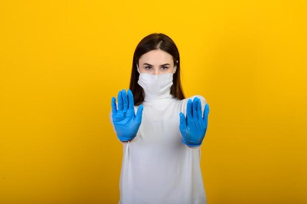 Fille en gants médicaux habille un masque médical sur son visage sur un fond blanc. maladie respiratoire. covid-19