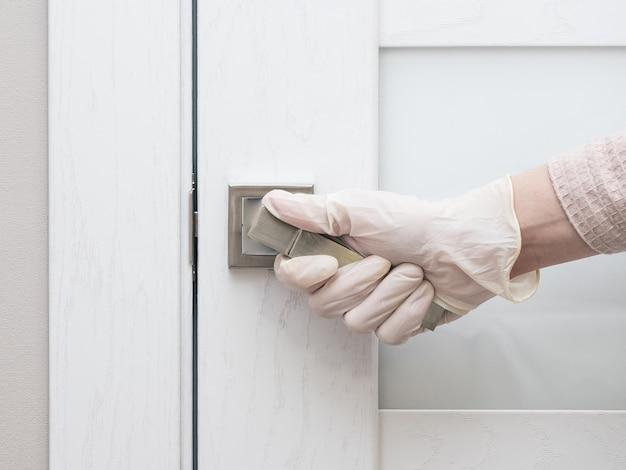 Une fille en gants médicaux ouvre une porte dans un lieu public.