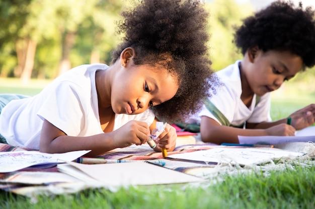 Fille et garçon afro-américains dessinent et peignent dans le parc. ils utilisent leur imagination et leur créativité dans l'art apprendre des idées en dehors de la salle de classe