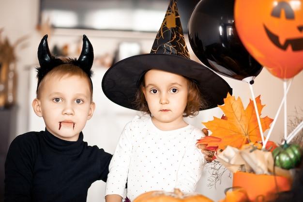 Une fille et un garçon drôles en costumes de sorcière et de mal pour halloween s'amusent.