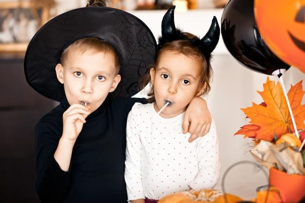 Fille et garçon drôles d'enfant en costumes de sorcière et de mal pour halloween, manger des bonbons et s'amuser.