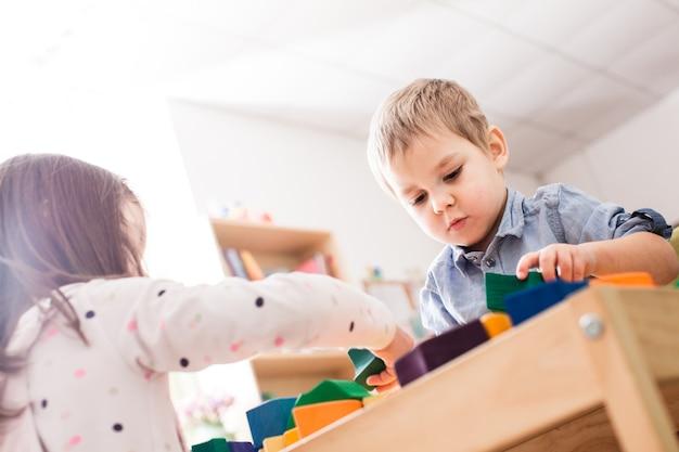 Fille et garçon jouant avec des cubes en bois colorés