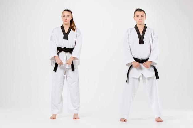 La fille et le garçon de karaté avec des ceintures noires