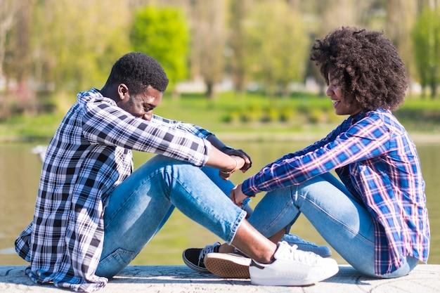 Une fille et un garçon noirs s'amusent et s'amusent ensemble dans des activités de loisirs en plein air près d'un parc