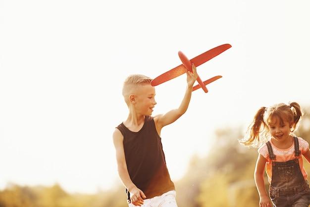 Fille et garçon s'amusant à l'extérieur avec un avion jouet rouge dans les mains.