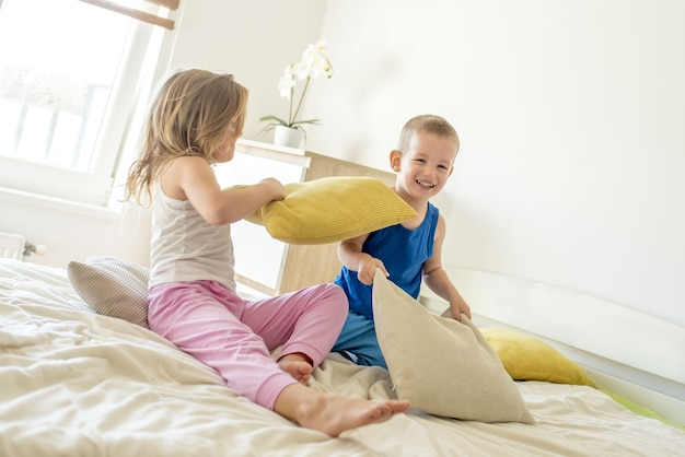 Fille et un garçon souriant et ayant une bataille d'oreillers sur un lit