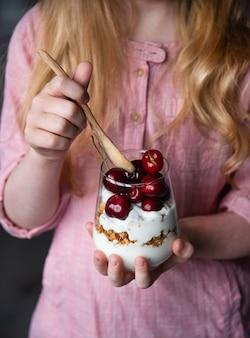 Fille garder dans le verre à la main avec dessert de cerise fraîche et yogourt naturel