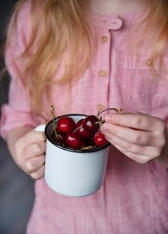 Fille garder une tasse de cerise fraîche à la main