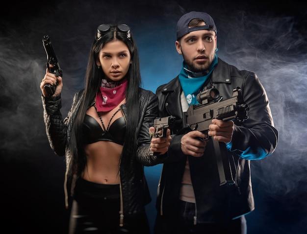 La fille et un gars dans une veste en cuir avec une arme à feu