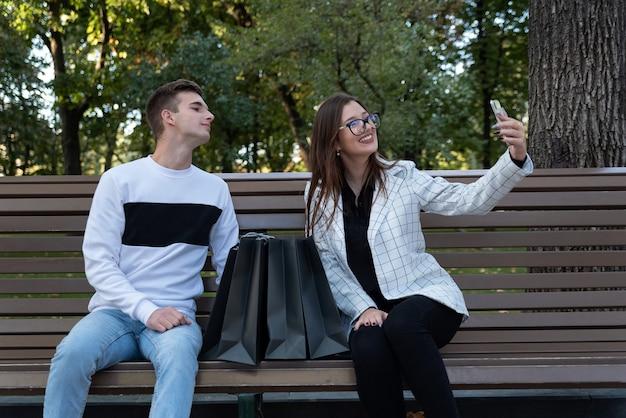 Une fille et un gars heureux prennent un selfie sur un banc avec des sacs à provisions. jeune mari et femme se reposant après avoir fait du shopping sur un banc dans un parc.