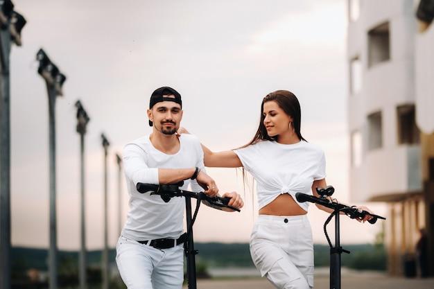 Une fille et un gars marchent sur des scooters électriques dans la ville, un couple amoureux sur des scooters.