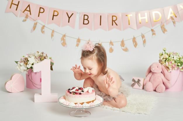Fille avec un gâteau d'anniversaire, séance photo d'un bébé d'un an