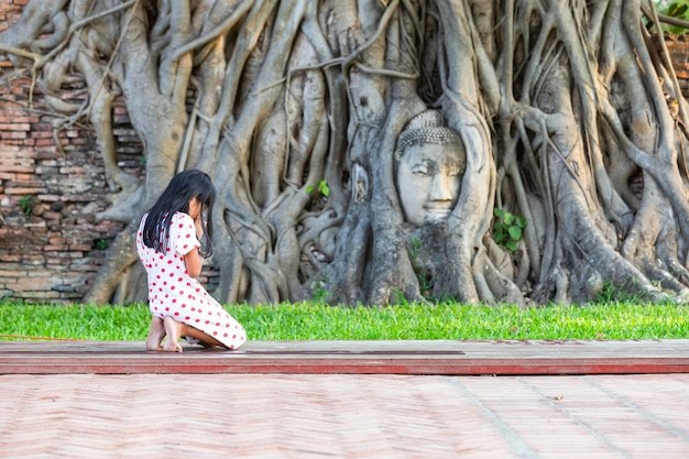 Une fille à genoux prier pour saint à la tête de la statue de bouddha dans les racines des arbres au wat mahathat dans la province d'ayutthaya, thaïlande