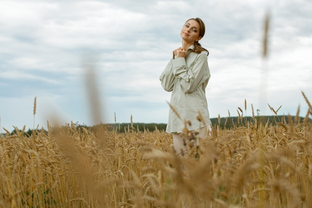 Fille gentille et douce dans des vêtements légers, debout au milieu du champ.