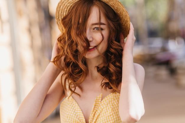 Fille de gingembre de bonne humeur en vêtements jaunes posant sur la rue floue. femme rousse raffinée au chapeau, passer du temps en ville.