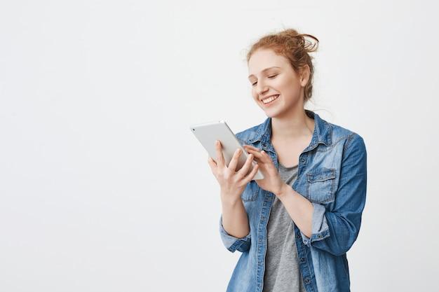 Fille de gingembre européenne ludique positive avec coiffure chignon tenant la tablette tout en tapant ou en naviguant sur le net