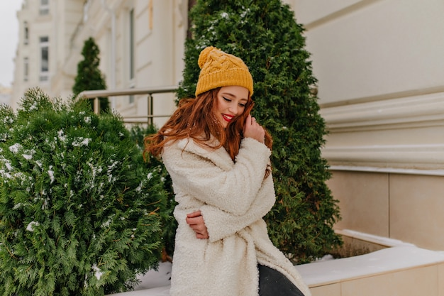 Fille de gingembre extatique posant près de sapin avec un sourire sincère. agréable femme européenne en blouse blanche debout à l'extérieur.