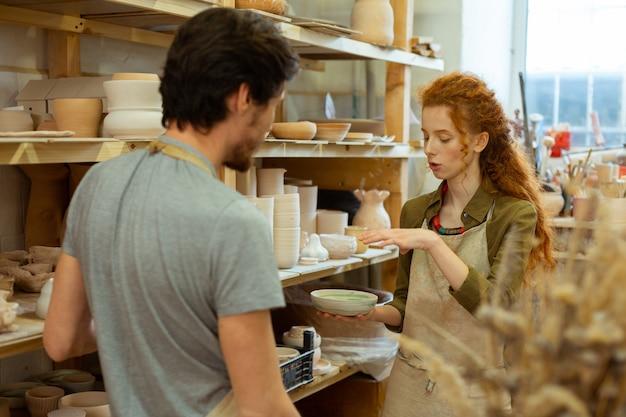 Fille de gingembre qui parle. femme active aux cheveux longs expliquant son idée à un homme attentif en utilisant une plaque d'argile comme exemple