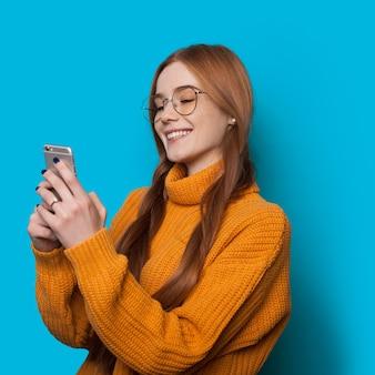 Fille de gingembre avec des taches de rousseur et des lunettes discutant avec quelqu'un à l'aide d'un mobile tout en posant sur un mur bleu