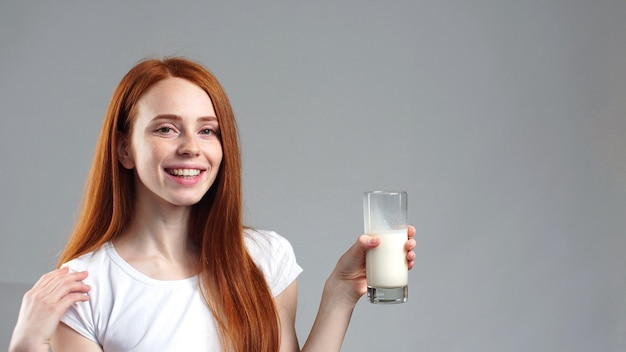 Fille de gingembre tenant un verre de lait. jeune fille joyeuse tenant un verre de gros plan de lait. mur gris isolé. mode de vie sain