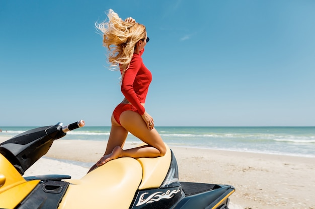 Fille glamour en bikini rouge sur le scooter des mers. modèle de bikini corps parfait longs cheveux blonds. sports nautiques, mode de vie estival. océan bleu sur fond.