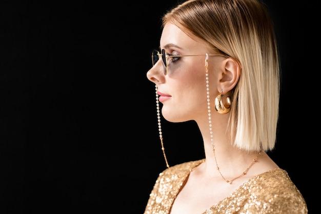 Fille glamour blonde dans des lunettes de soleil élégantes, robe chic et boucles d'oreilles dorées debout devant la caméra avec copyspace sur la gauche