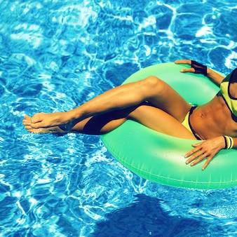 Fille glamour avec cercle gonflable en fête au bord de la piscine summer style