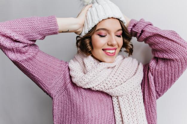 Fille glamour avec coupe de cheveux courte posant en écharpe avec les yeux fermés. femme blanche détendue en bonnet tricoté bénéficiant d'une séance photo en tenue d'hiver.