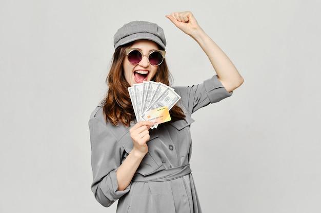 Fille glamour détient de l'argent dollars et une carte de crédit bancaire avec surprise