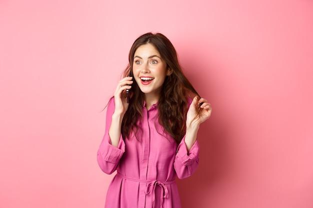 Fille glamour parlant au téléphone et jouant avec les cheveux, l'air heureuse et détendue pendant la conversation, appelant un ami, debout contre le mur rose.