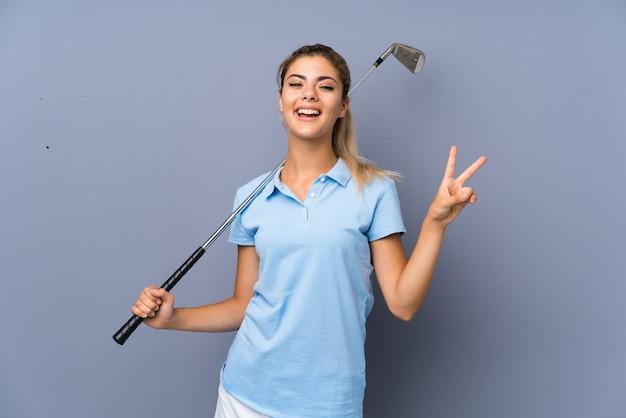 Fille de golfeur adolescent sur mur gris souriant et montrant le signe de la victoire