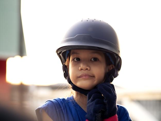 Fille de gosse d'école asiatique à cheval, équitation ou pratique de l'équitation au ranch.