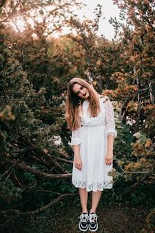 Fille gothique en robe vintage blanche posant contre les buissons dans le parc d'été.