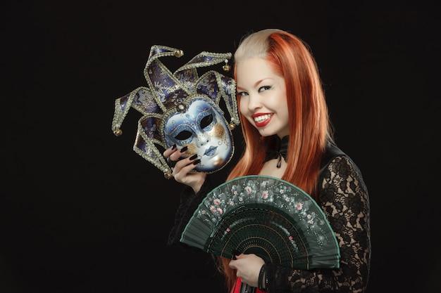 Fille gothique avec ventilateur et un masque