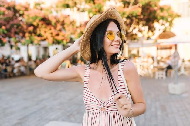 Fille gracieuse inspirée portant des lunettes à la mode et un chapeau d'été, passer du temps à l'extérieur, profiter d'une journée chaude