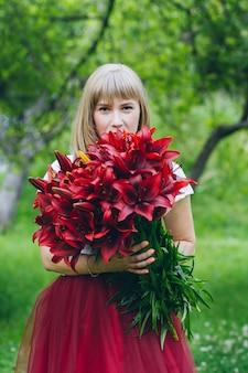 Fille avec un grand bouquet de lys violets