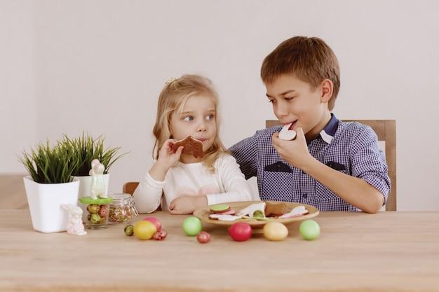 Une fille avec un grand frère est assise à la table des fêtes et pose des biscuits et des œufs de pâques